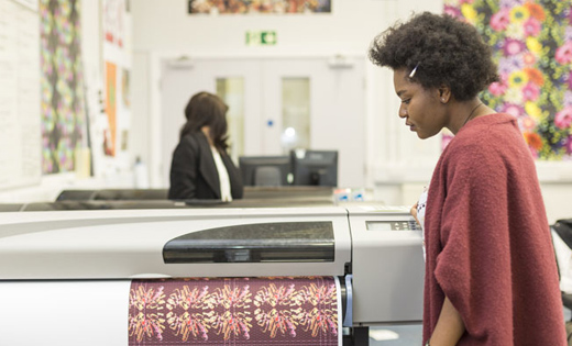 A person leaning over the textiles printing machine.