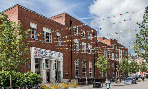A shot of the outside of the Refectory building, with bunting up over the plaza. October 2020.