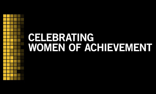 "The Women of Achievement slogan - ""Celebrating Women of Achievement"" against a black and yellow background. February 2021"